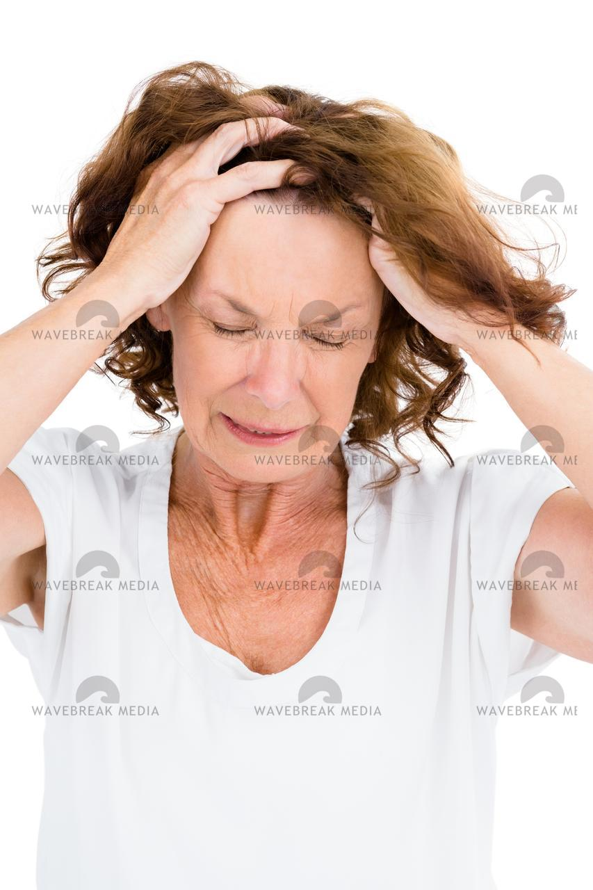 """Irritated mature woman with head in hands"" stock image"
