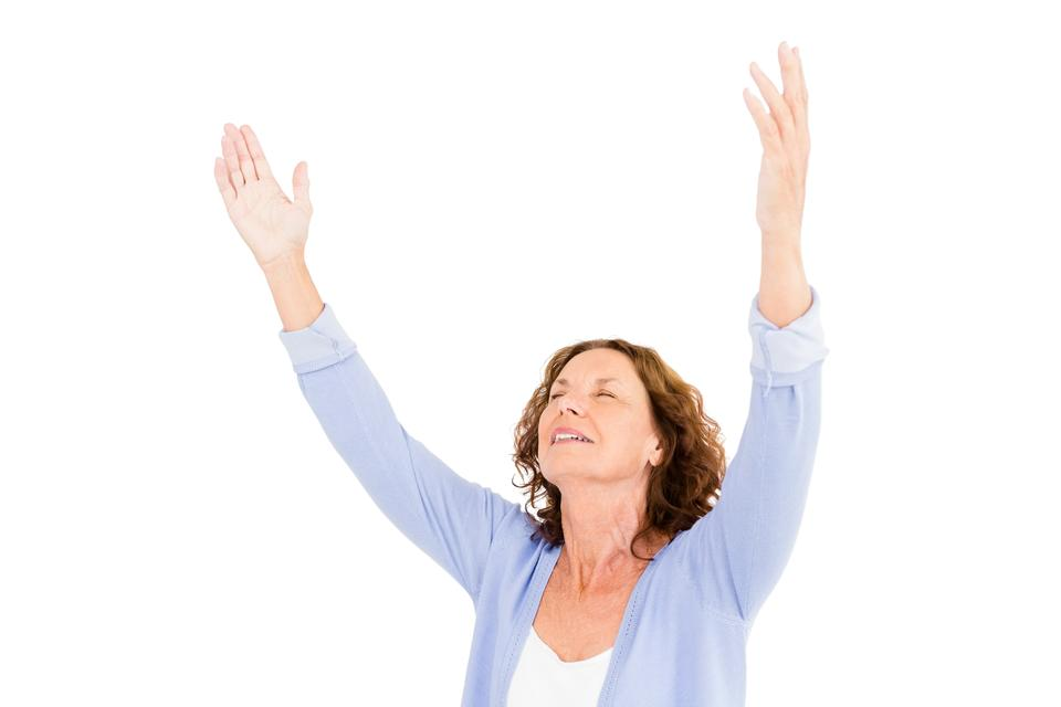 """""""Close-up of mature woman with arms raised while praying"""" stock image"""