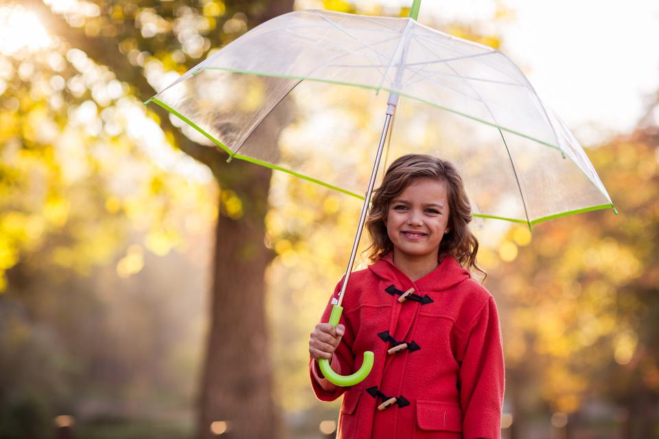 """Portrait of cute girl with umbrella at park"" stock image"