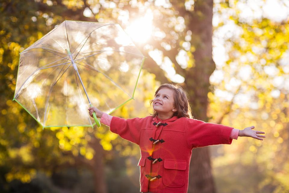 """Smiling girl holding umbrella at park"" stock image"