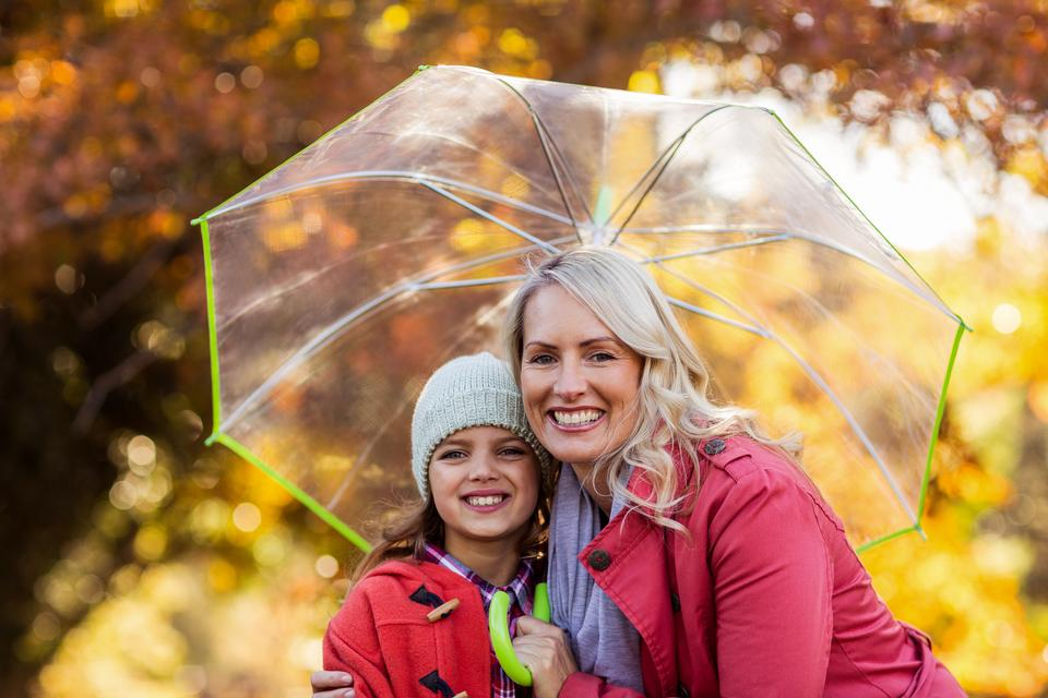 """Mother and daughter embracing while holding umbrella"" stock image"