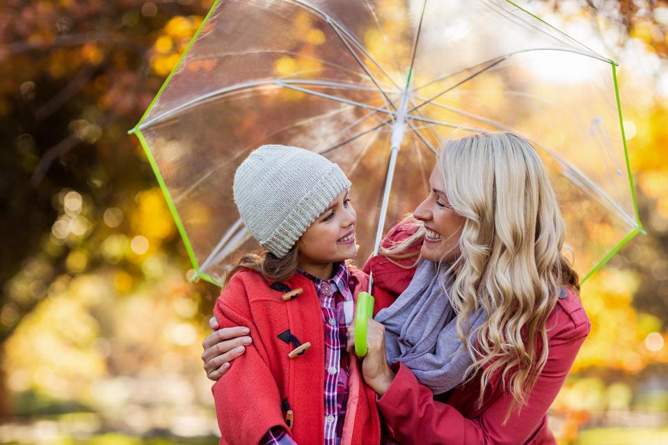 """Happy mother and daughter holding umbrella at park"" stock image"