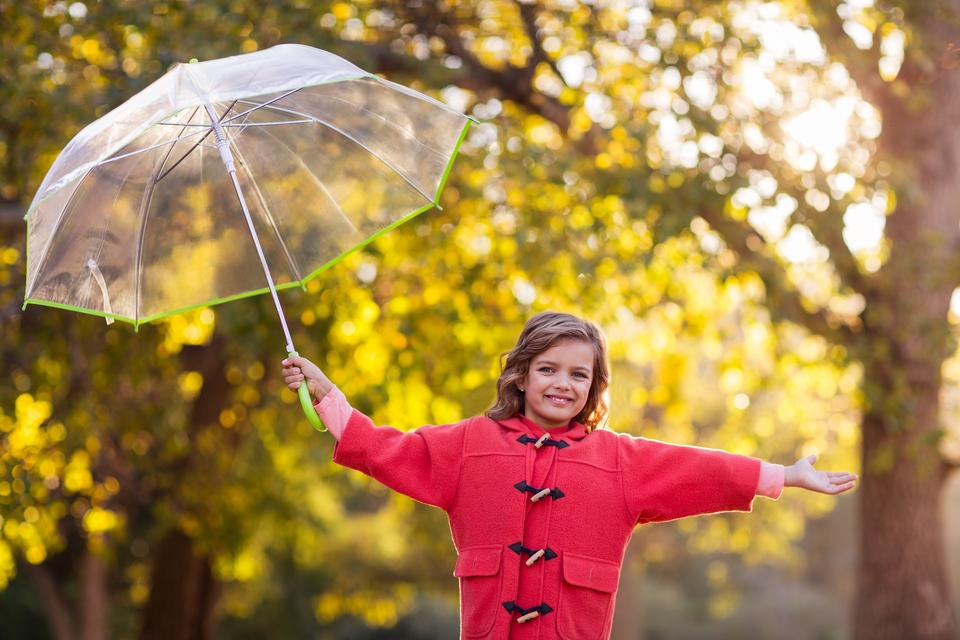 """Girl playing with umbrella at park"" stock image"