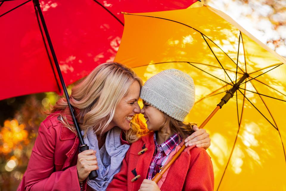 """Cheerful mother and daughter with umbrella at park"" stock image"