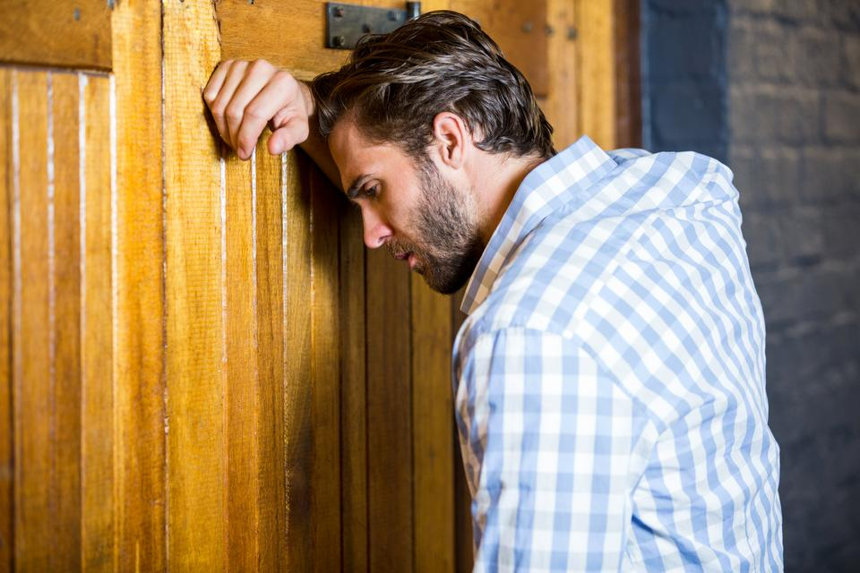 """Depressed man leaning on door"" stock image"