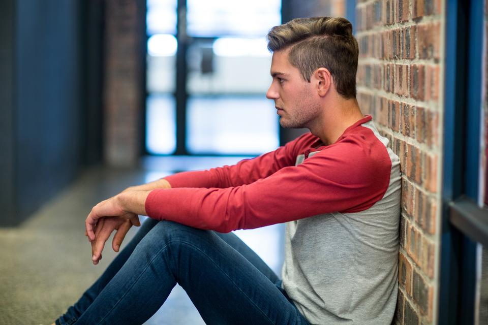 """Stressed man sitting by wall"" stock image"