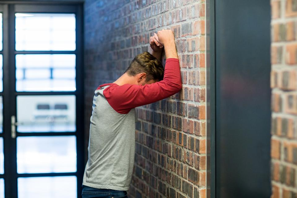 """Side view of stressed man leaning on wall"" stock image"
