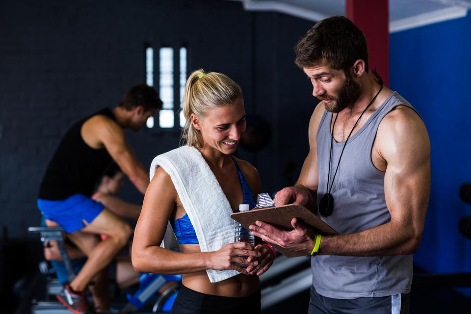 """Fitness instructor discussing with woman in gym"" stock image"