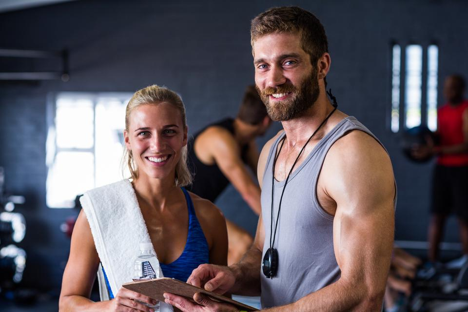 """Portrait of smiling fitness instructor with woman in gym"" stock image"