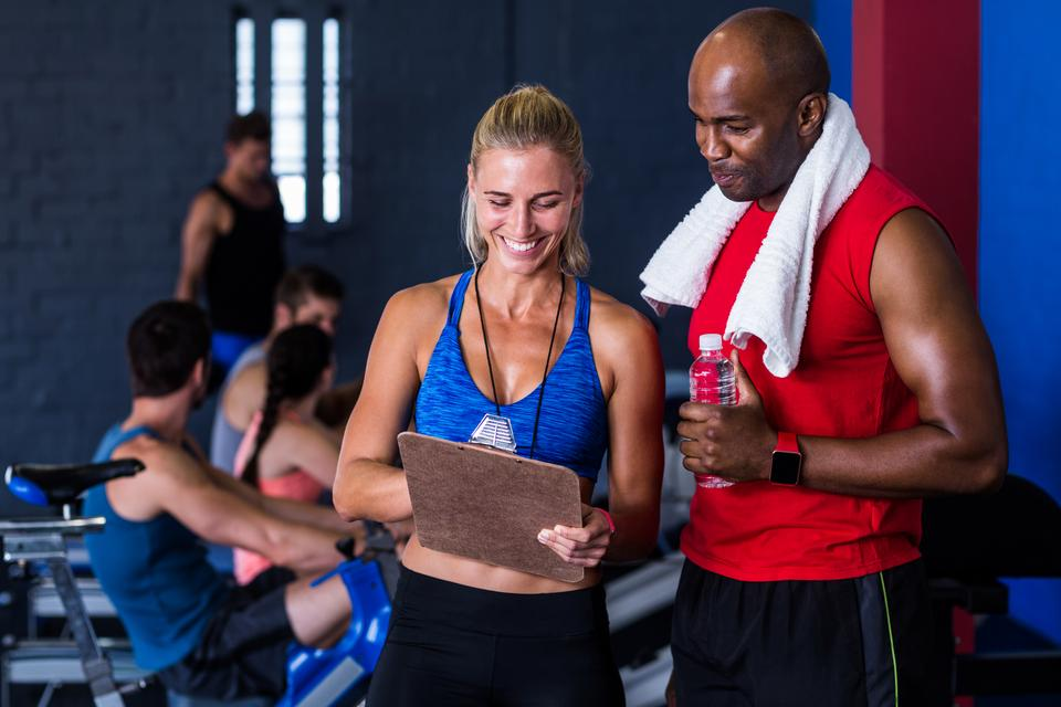 """Smiling fitness instructor discussing with man in gym"" stock image"