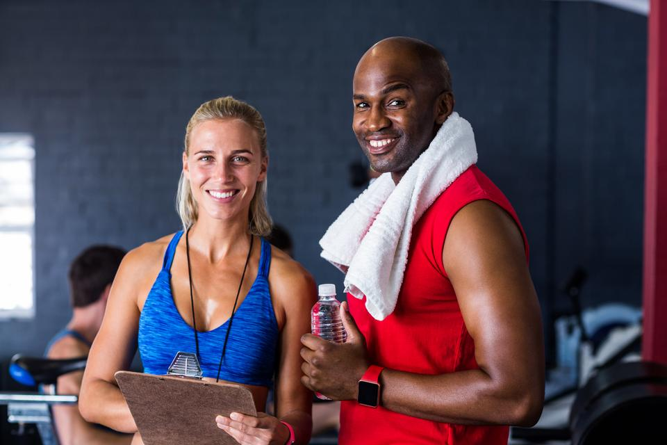 """Portrait of happy fitness instructor with man"" stock image"