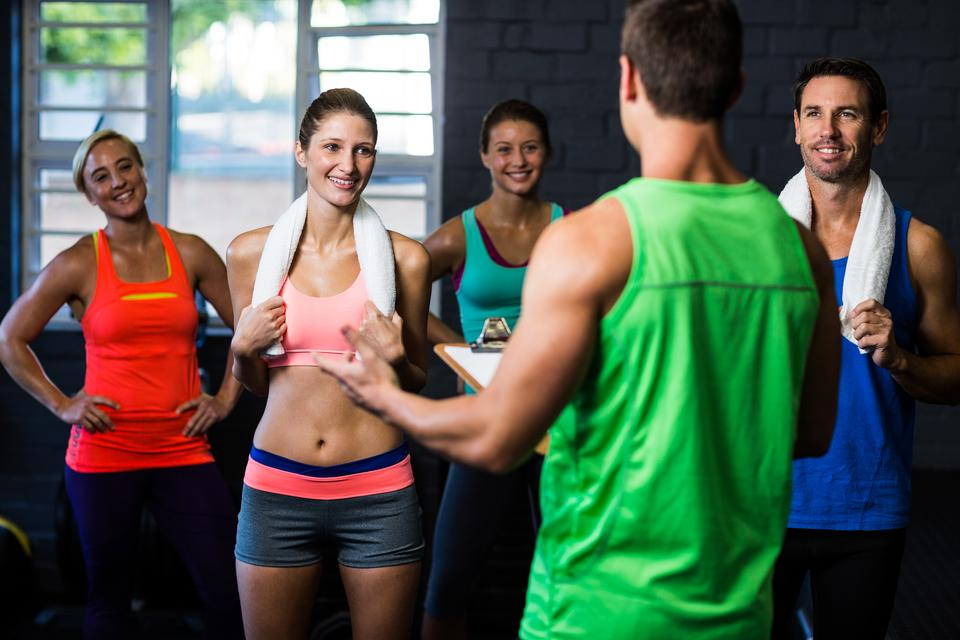 """Fitness instructor discussing with happy people"" stock image"