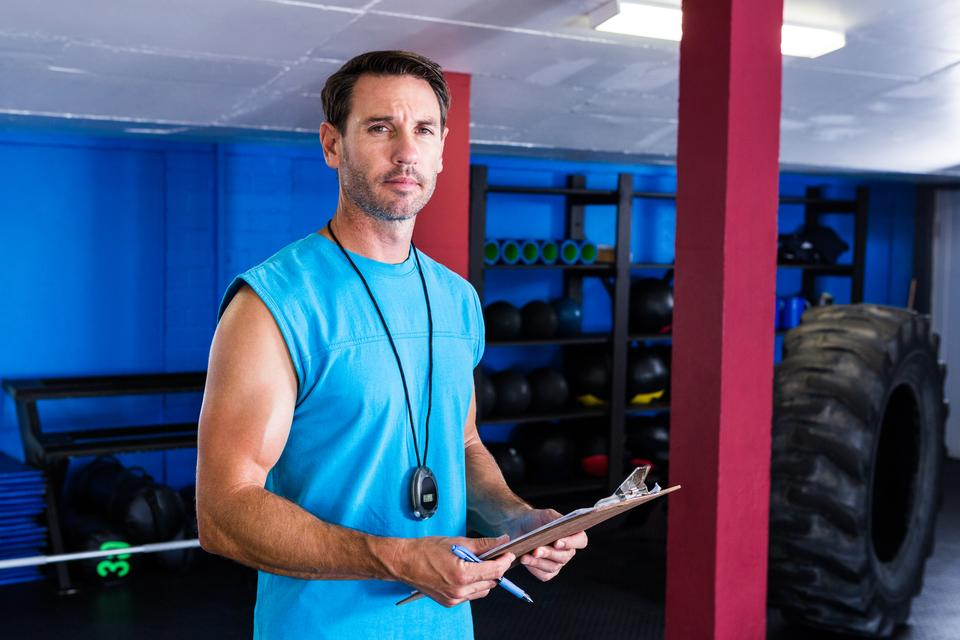"""Serious fitness instructor holding clipboard"" stock image"