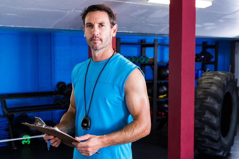 """Serious instructor holding clipboard in gym"" stock image"