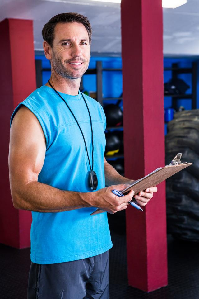 """Smiling fitness instructor holding clipboard"" stock image"