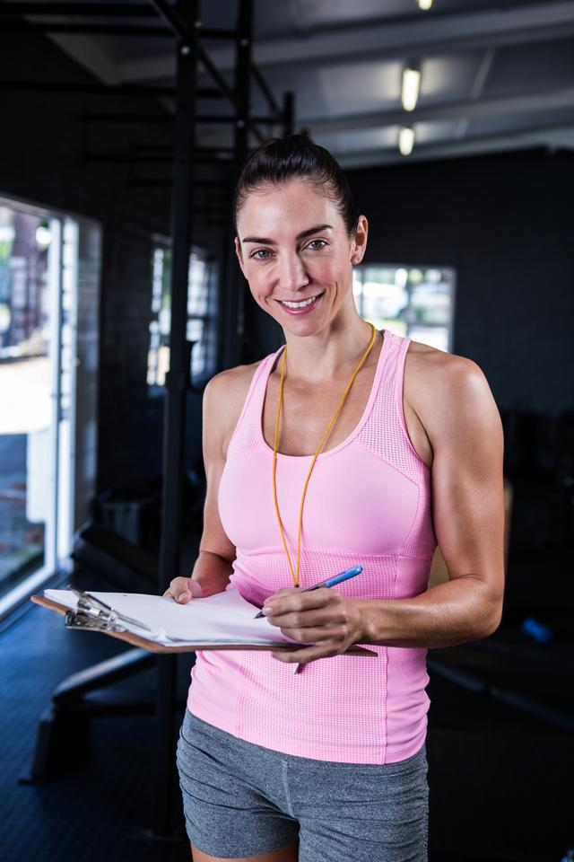 """Happy fitness instructor holding clipboard in gym"" stock image"