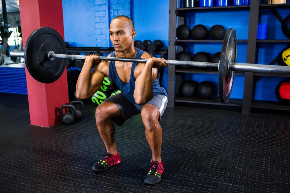 """Male athlete weightlifting in fitness studio"" stock image"