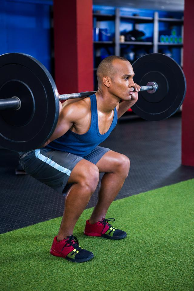 """Determined young man weightlifting"" stock image"