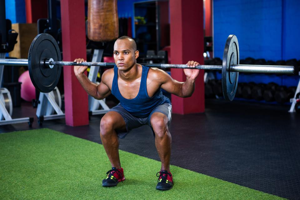 """Young man weightlifting in fitness studio"" stock image"