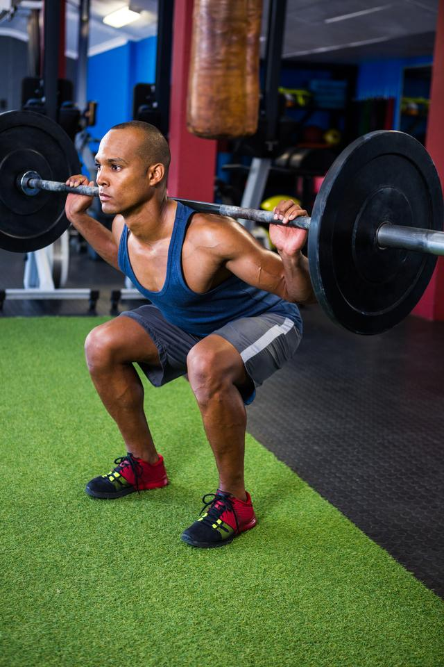 """Young man weightlifting in gym"" stock image"