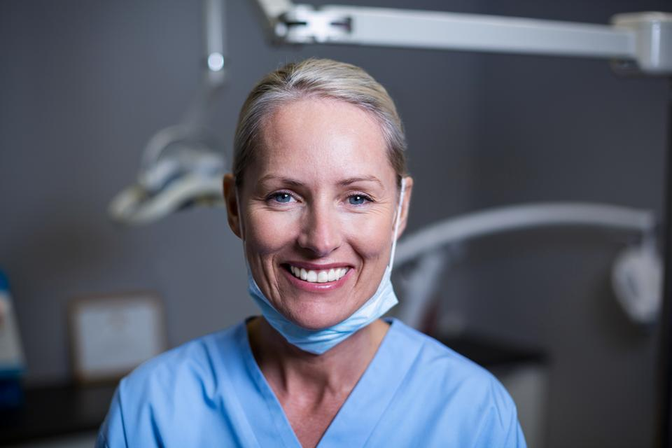 """Dental assistant smiling in clinic"" stock image"