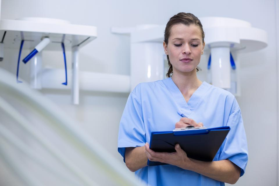 """Dental assistant holding clipboard"" stock image"