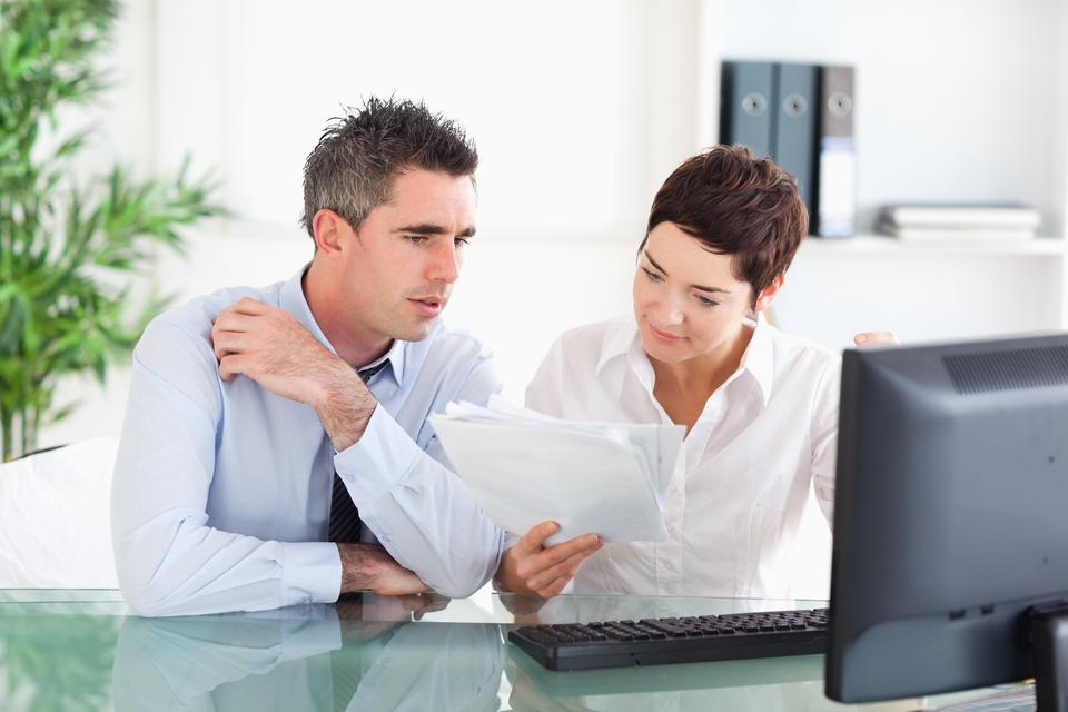 """""""Colleagues looking at folders"""" stock image"""