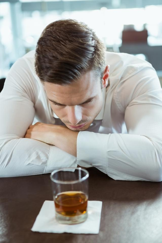 """Depressed man looking at alcohol glass"" stock image"