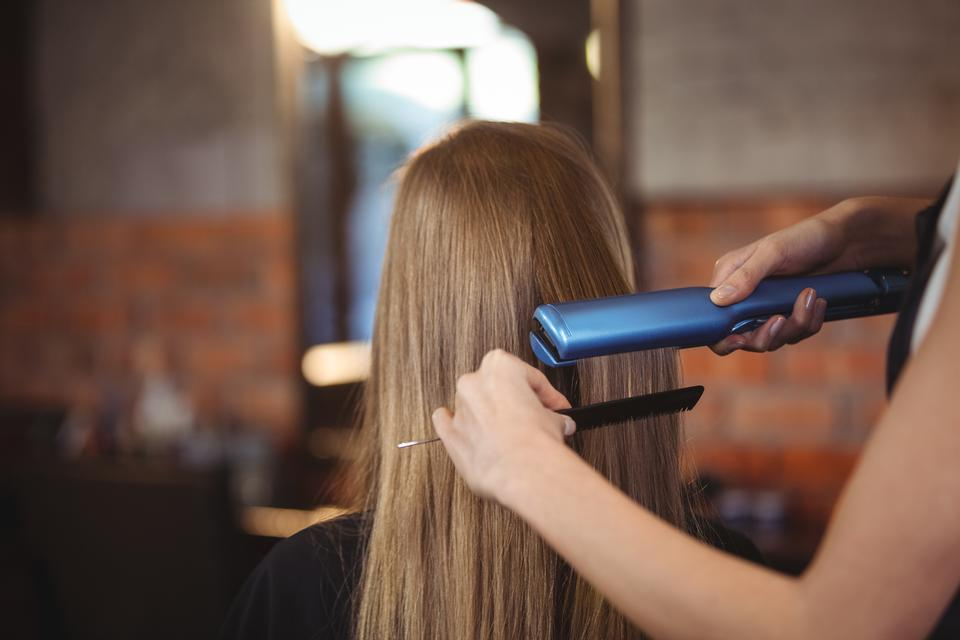 """""""Female hairdresser straightening the hair of a client"""" stock image"""
