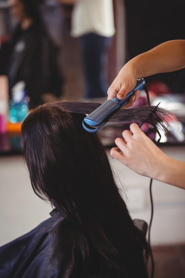 """""""Hairdresser straightening the hair of a client"""" stock image"""