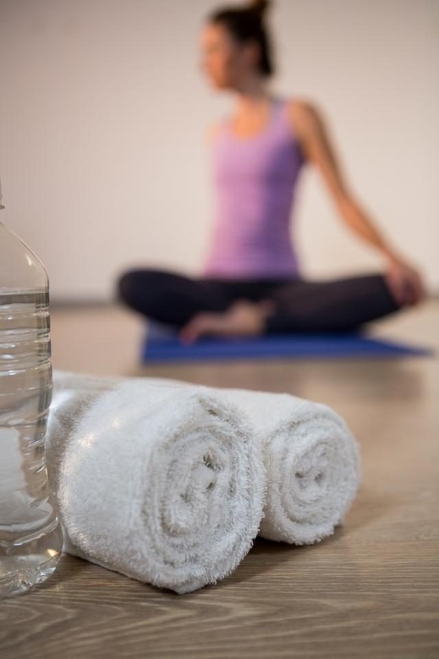 """""""Rolled towels and water bottle in fitness studio"""" stock image"""