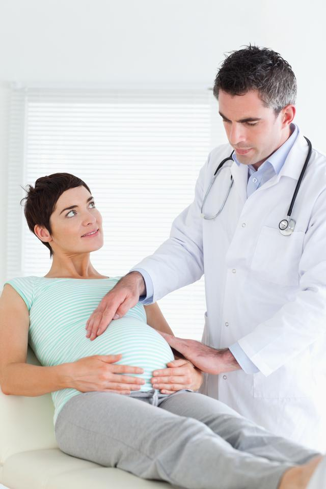 """""""Doctor examining a pregnant womans tummy"""" stock image"""