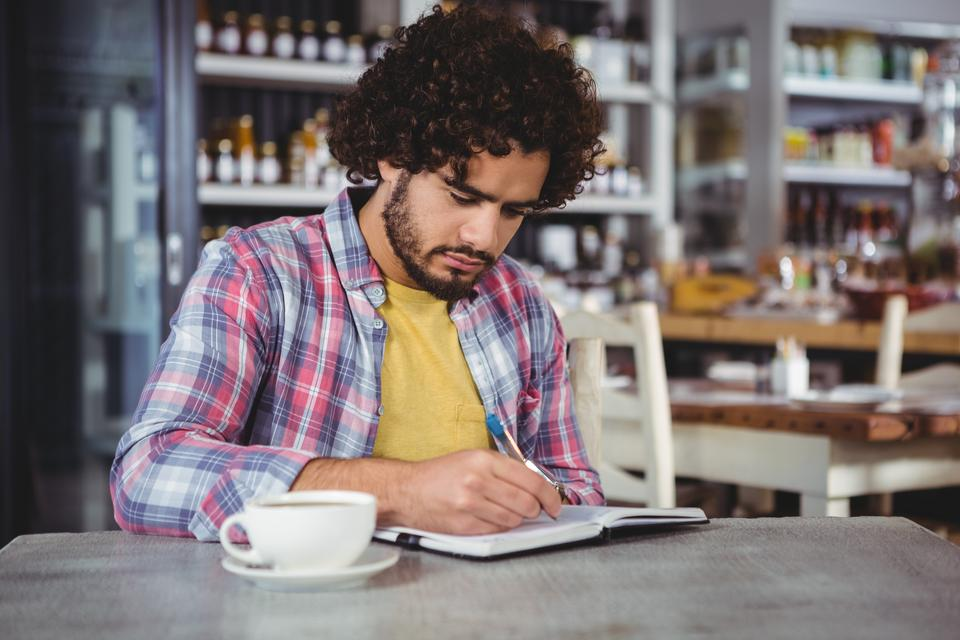 """Man writing on a diary"" stock image"