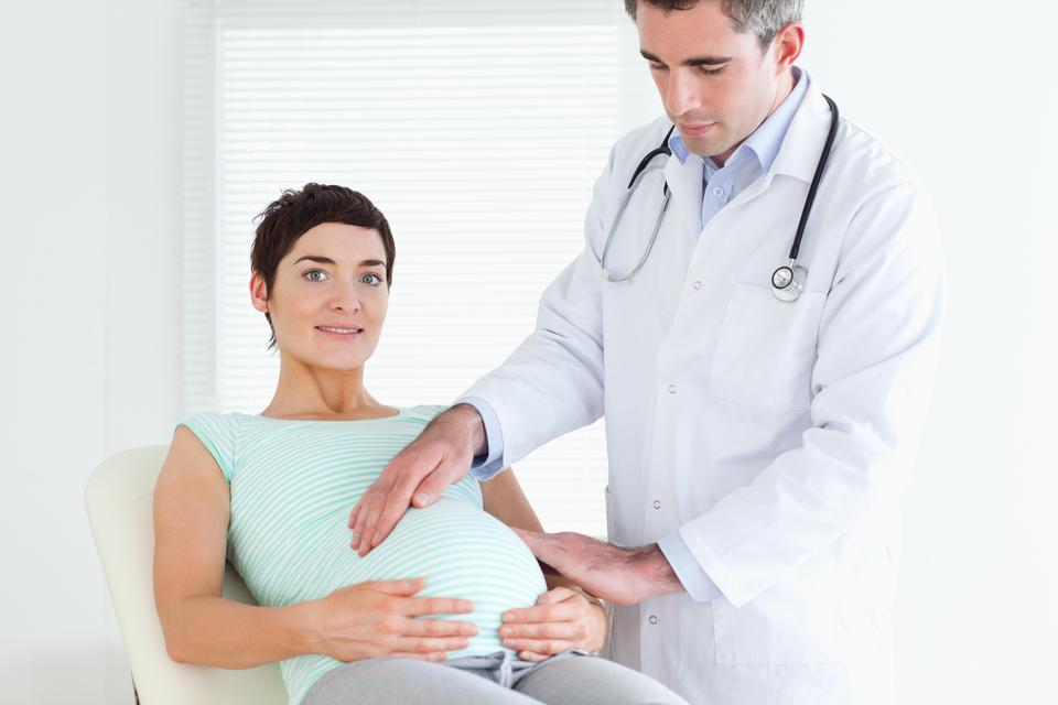 """""""Male Doctor ausculating a pregnant womans tummy"""" stock image"""