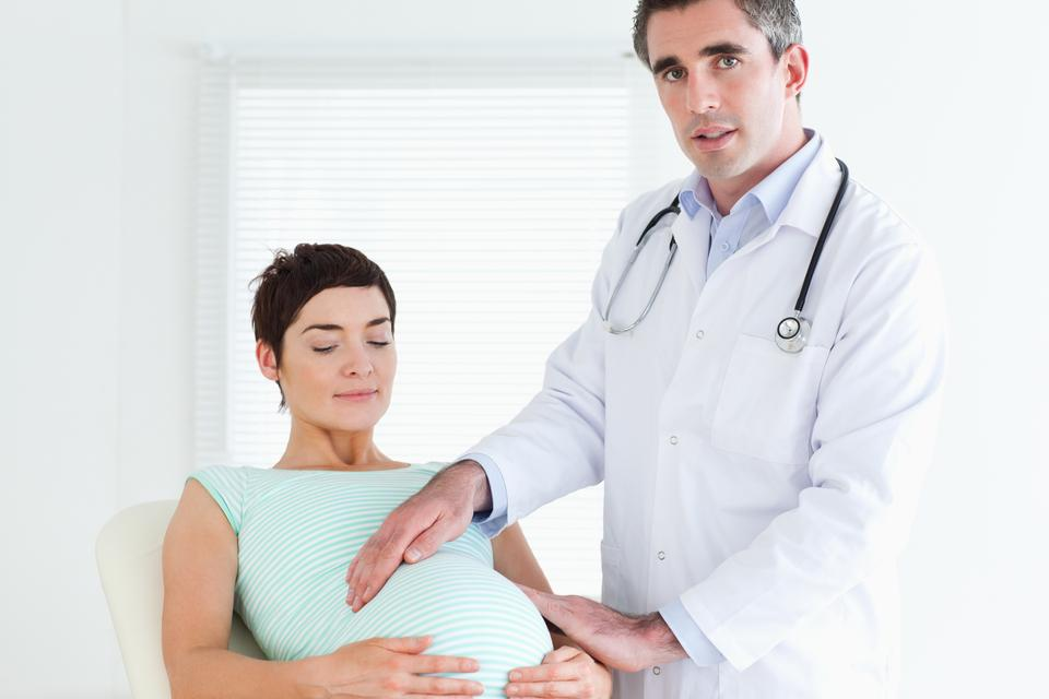 """""""Male Doctor examining a pregnant womans tummy"""" stock image"""