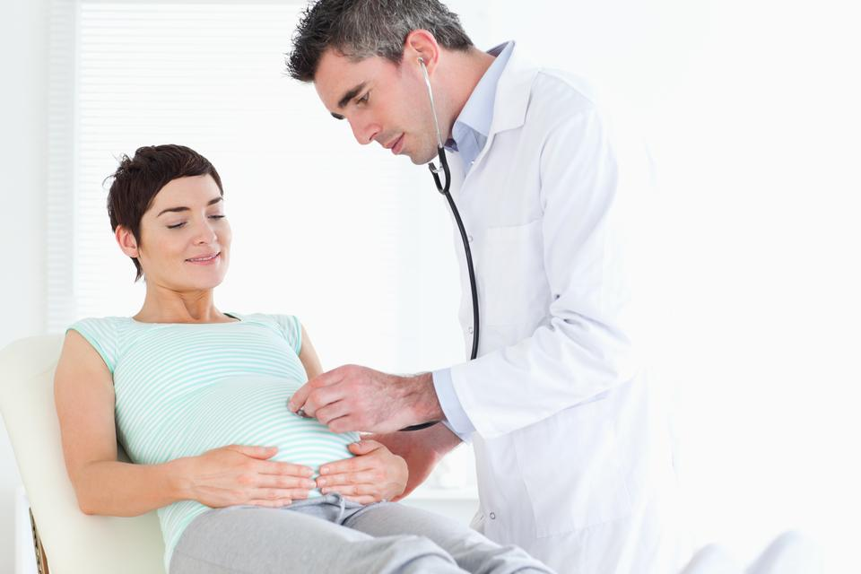 """""""Doctor listening into the womans tummy with a stethoscope"""" stock image"""