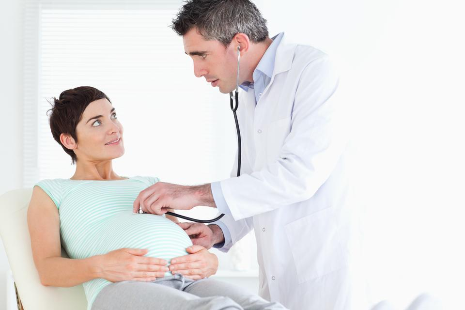"""""""Doctor examining the womans tummy with a stethoscope"""" stock image"""