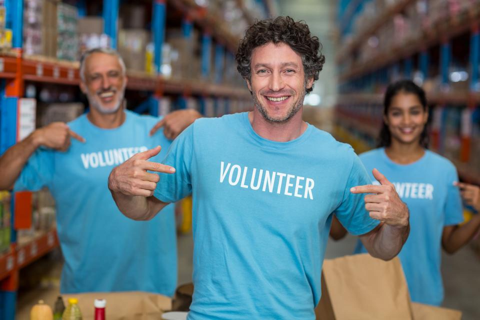 """Portrait of volunteers pointing at t-shirt"" stock image"