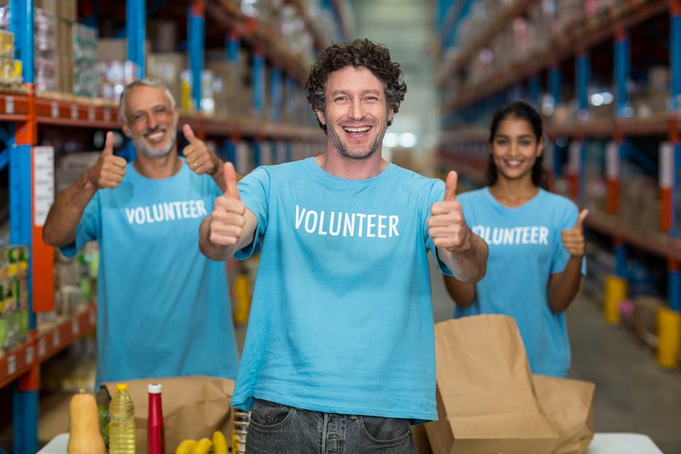 """Portrait of volunteers showing thumbs up"" stock image"