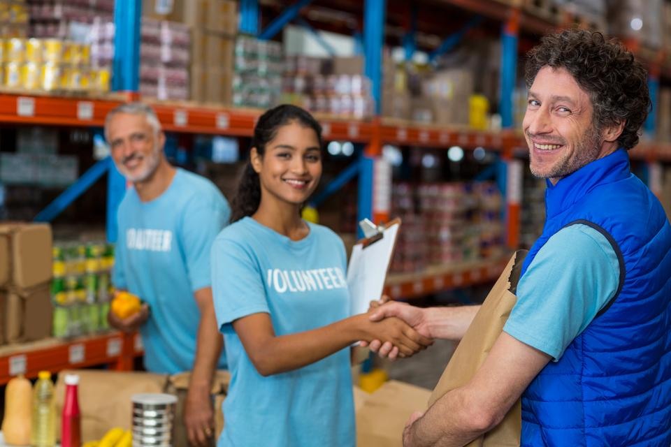 """Portrait of volunteers shaking hands while working"" stock image"