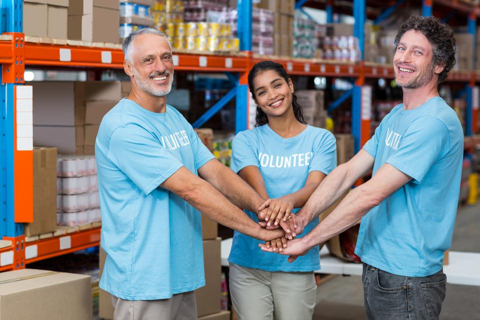 """Portrait of happy volunteers putting hands together"" stock image"