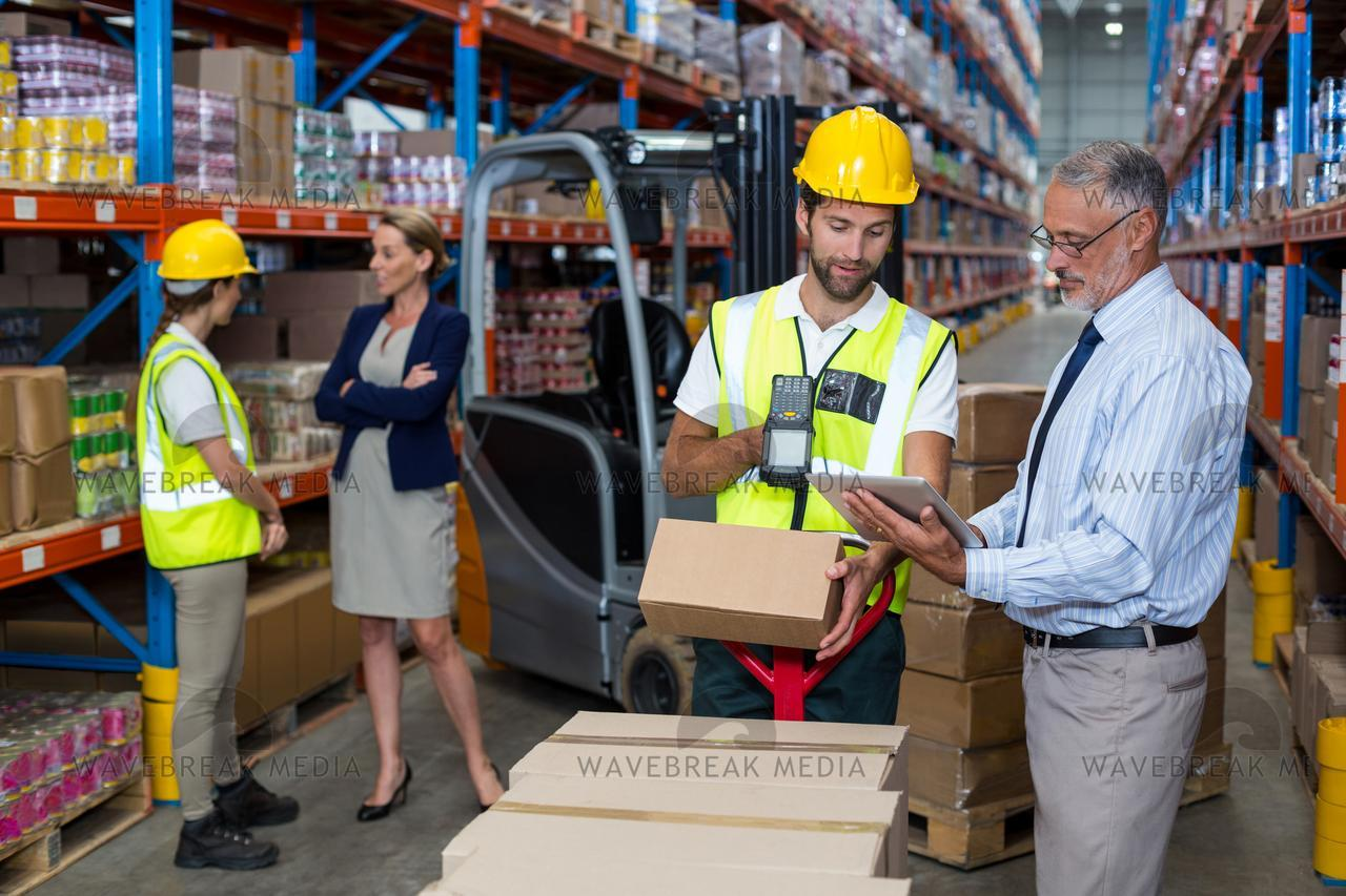 Warehouse manager holding digital tablet while male worker