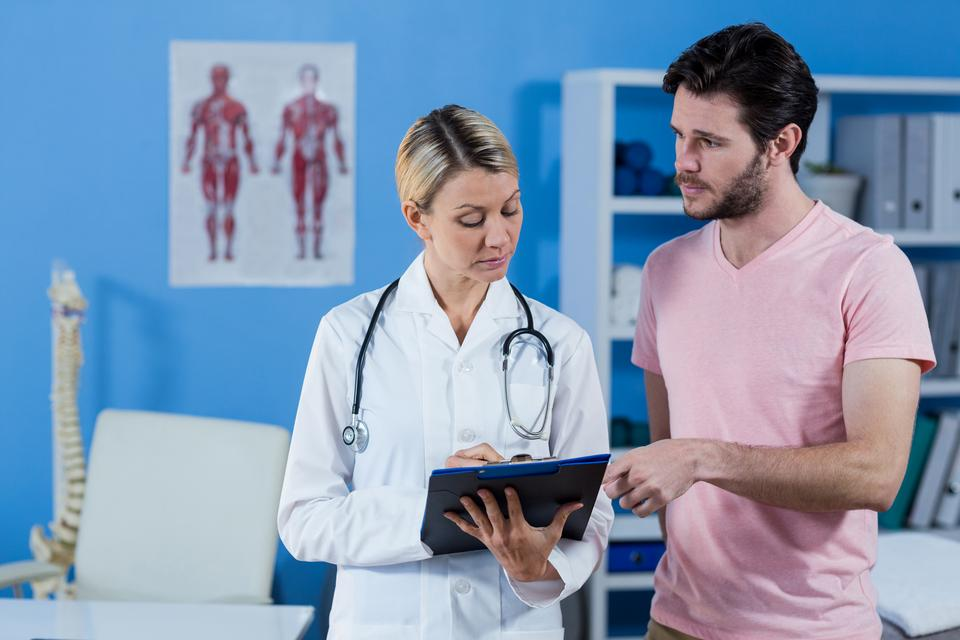 """Physiotherapist explaining diagnosis to male patient"" stock image"