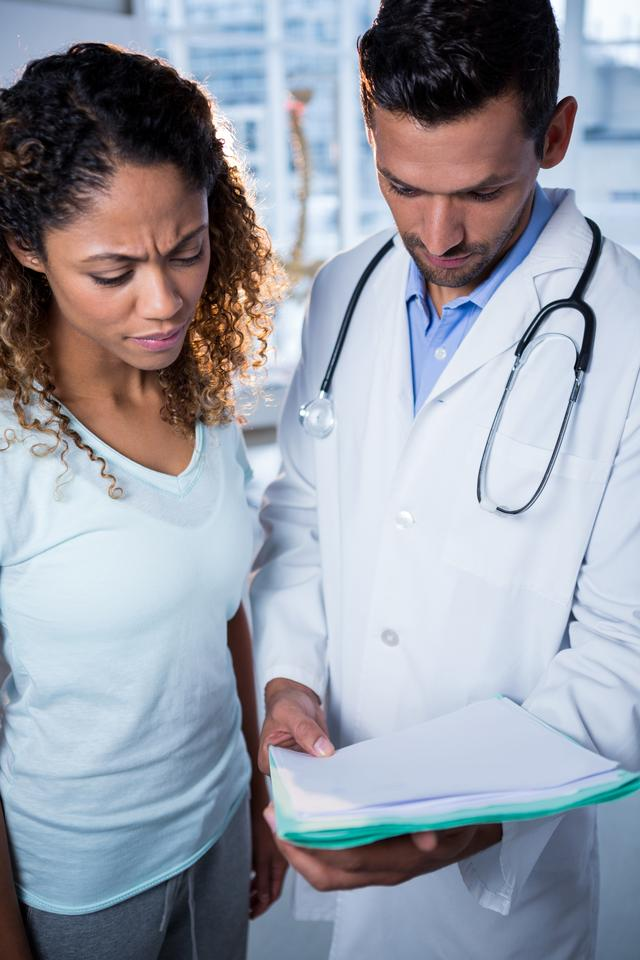 """Physiotherapist explaining diagnosis to female patient"" stock image"