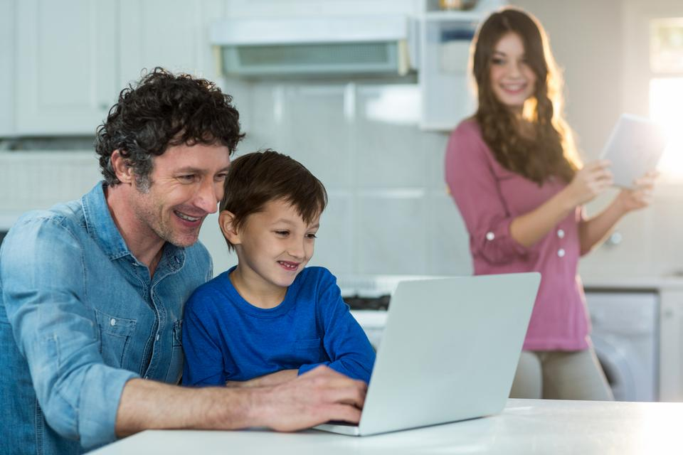 """""""Family using digital tablet and laptop"""" stock image"""