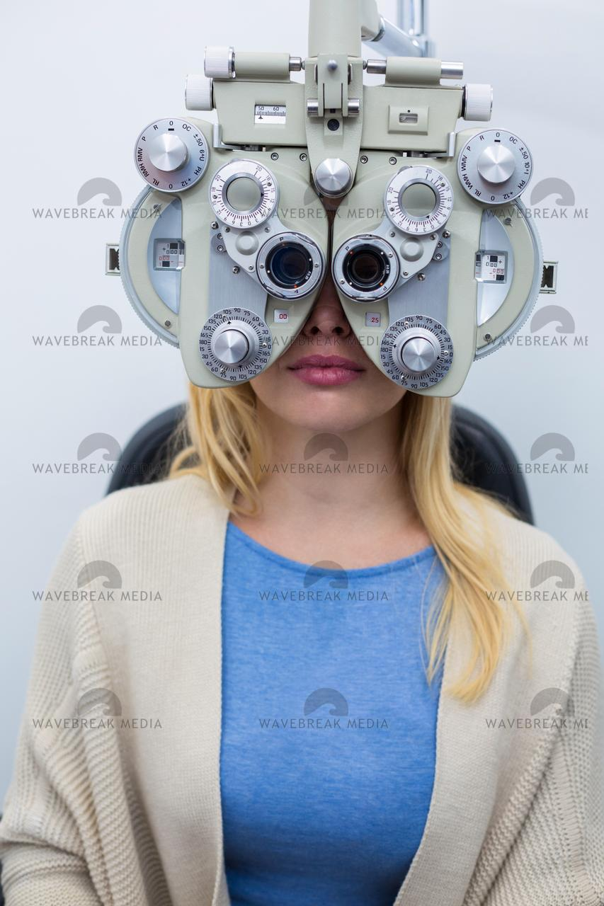 Female patient looking through phoropter during eye examination