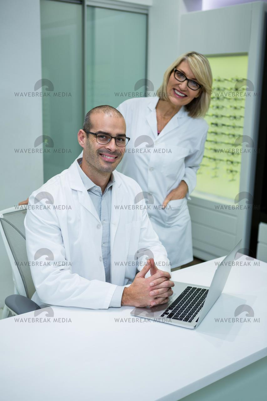Smiling optometrists in ophthalmology clinic - License