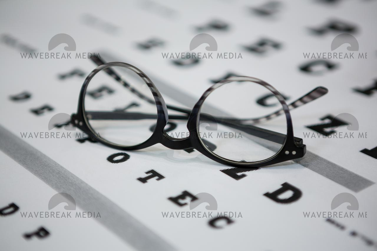Close-up of spectacles on eye chart - License, download or