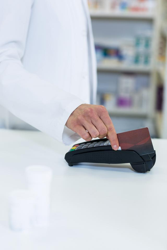 """""""Pharmacist swiping card through payment terminal"""" stock image"""