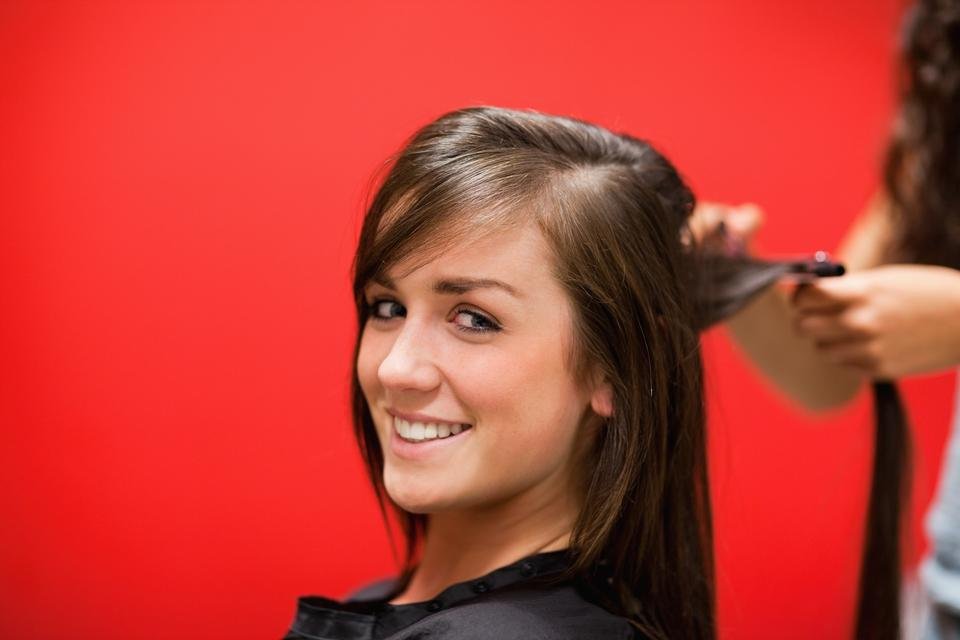 """Young woman having her hair straightened"" stock image"